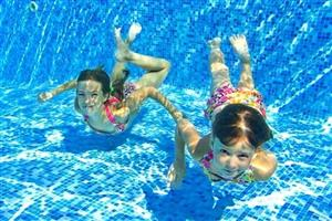 two girls swimming in a blue pool