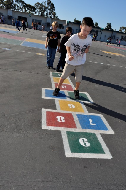 Student playing hopscotch during Physical Education