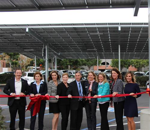 District and local dignitaries posed beneath Solana Pacific School solar panels preparing to cut the red ribbon