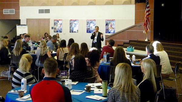 Image of Superintendent Terry Decker speaking in front of a group of parents, community members and staff members