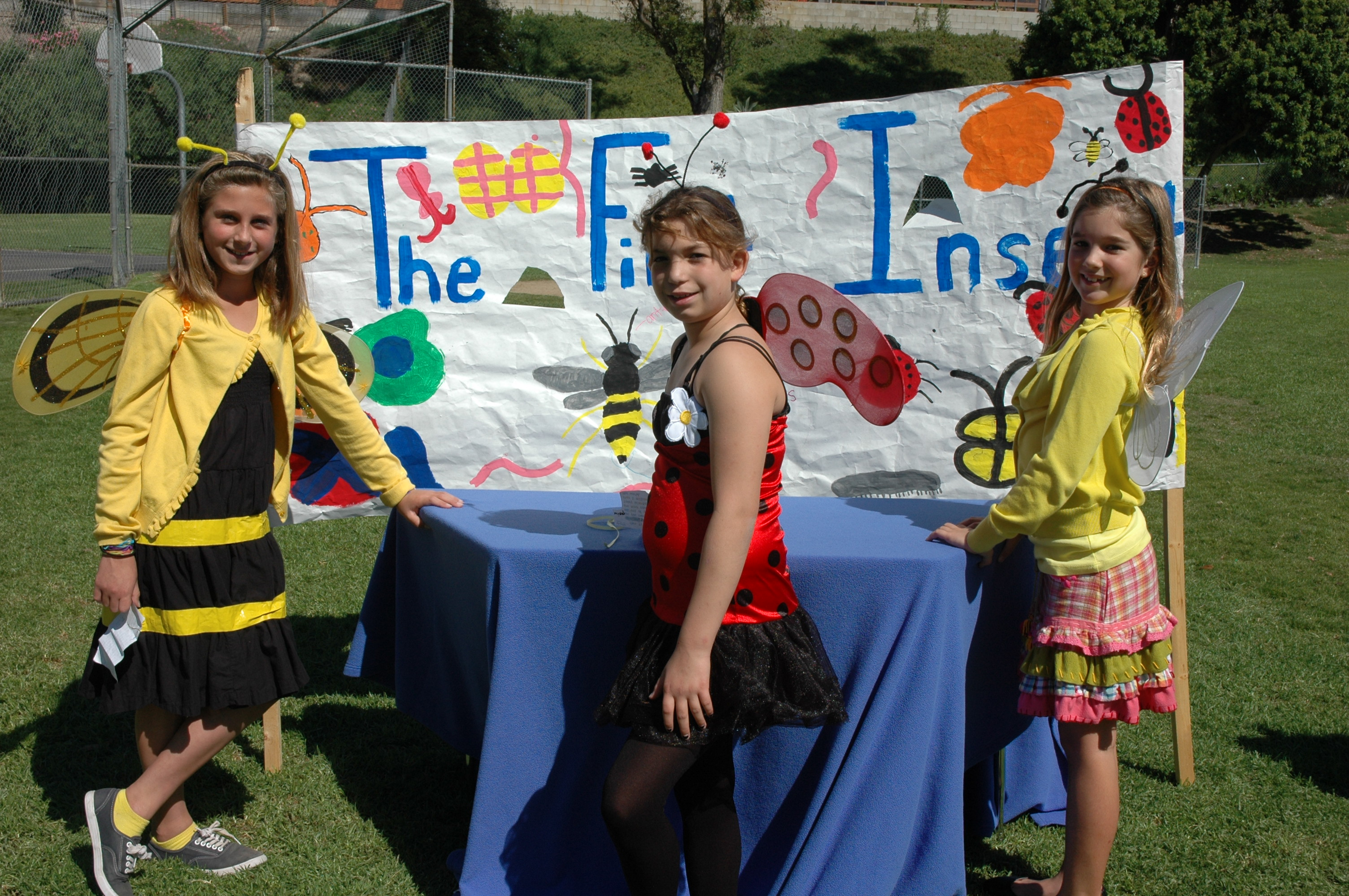 Students dressed as insects posing in front of their booth at our Earth's Timeline