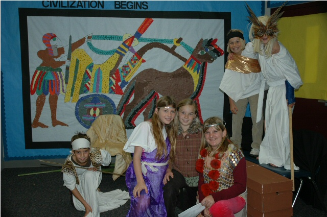 students dressed up for a play posing in front of a mosaic