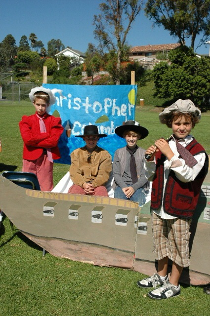 Boys dressed as Explorers posing in front of their Explorer's Fair booth