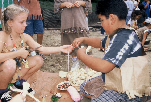 students are stringing beads during the Pow Wow