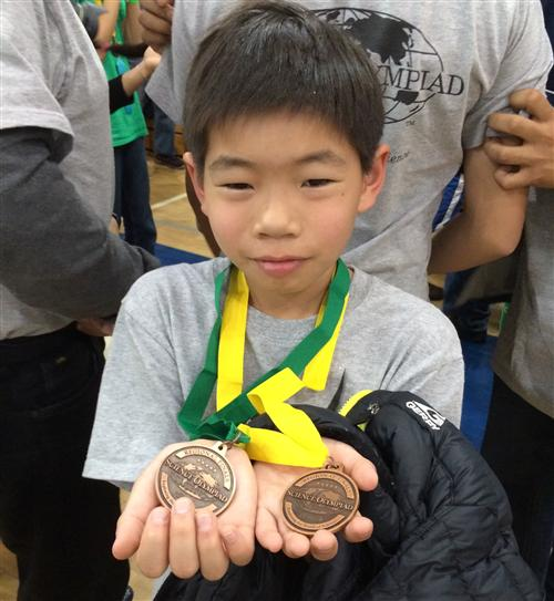 A child is holding his two Science Olympiad Medals